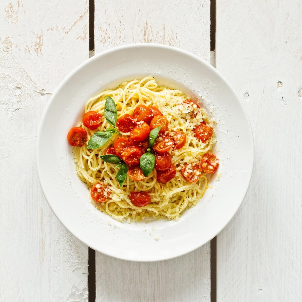 Spaghetti with tomato sauce on white wooden background